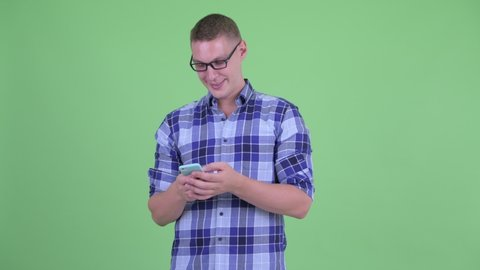 Happy young hipster man using phone