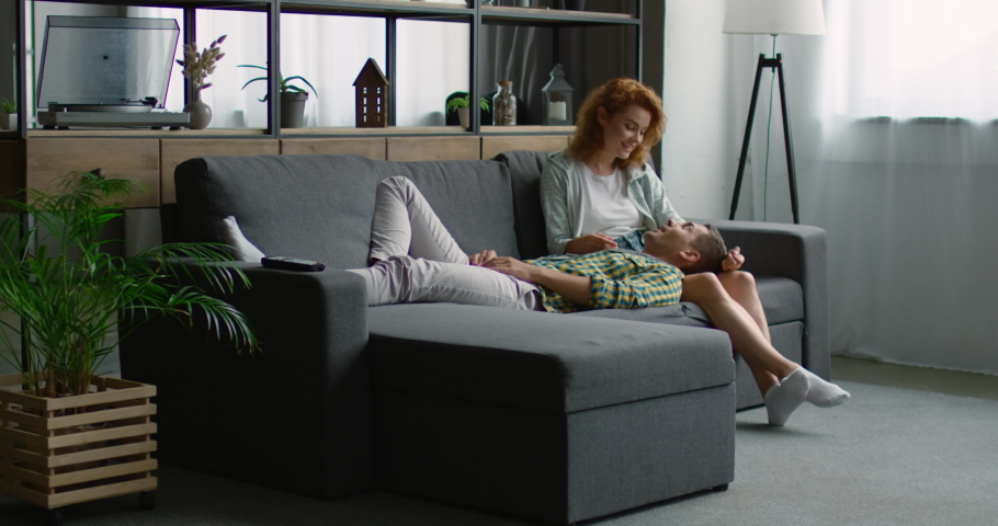 Happy young man and woman relaxing on a sofa, talking, enjoying their life, spending weekend together at home, Caucasian. 4K, shot on RED camera. | Shutterstock HD Video #1034642300