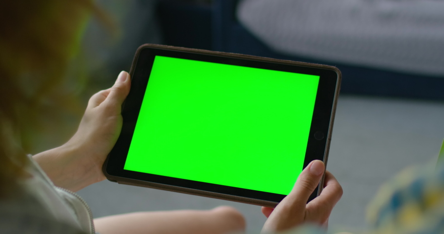 Woman using tablet computer, watching green screen on mobile device, chroma key, touching a screen, enjoying online entertainment at home, close up, 4K, shot on RED camera