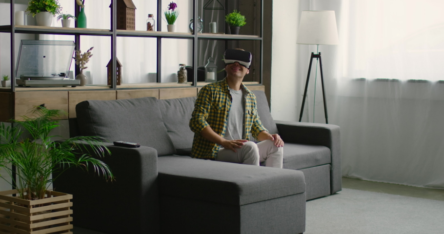 Young man is wearing virtual reality headset, using gestures to control images, rips and sniffs virtual fruits, enjoys 360 video imagination concept, sitting on sofa. 4K, shot on RED camera. | Shutterstock HD Video #1034642447