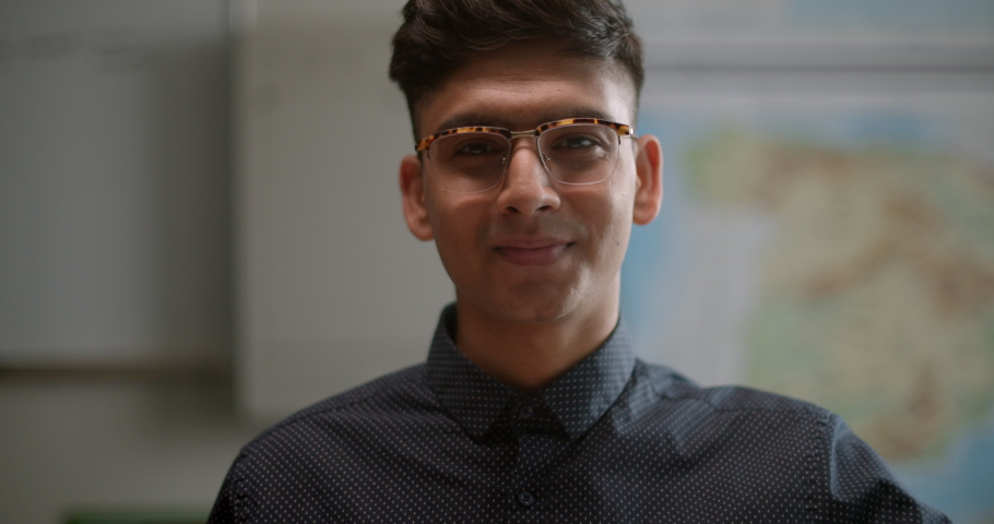 Portrait of young student in classroom wearing funky glasses, smiling and confident