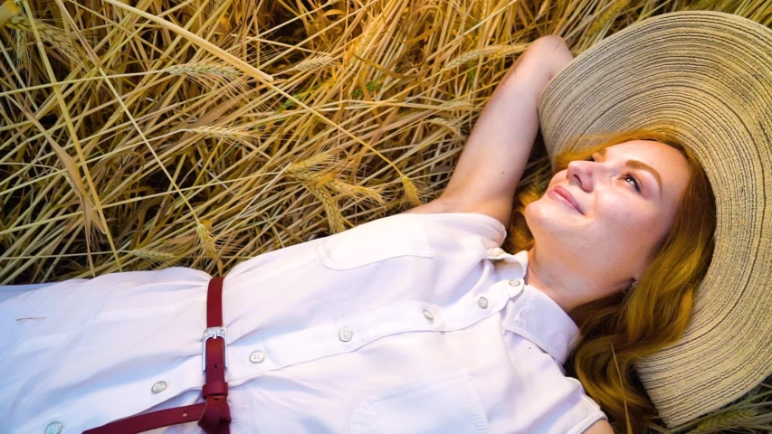 Above view spinning over young romantic red haired woman lying on wheat field | Shutterstock HD Video #1034661323
