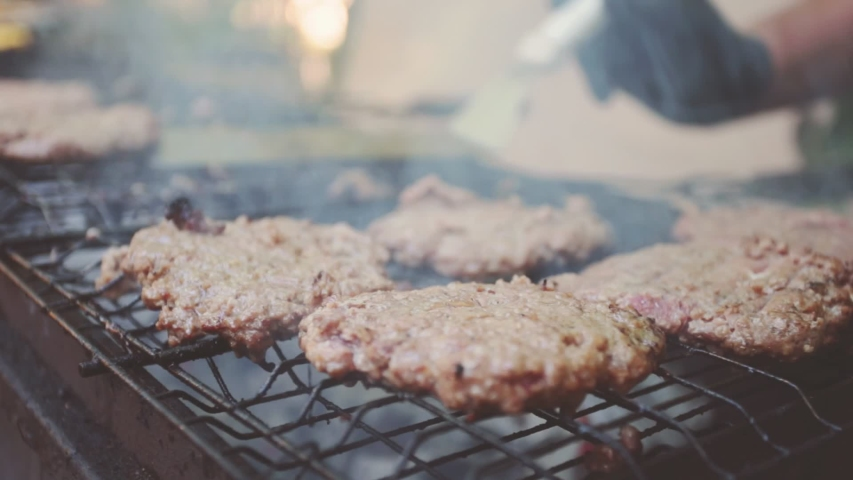 Man rearranges cooked meat for burgers on the grill | Shutterstock HD Video #1034663324