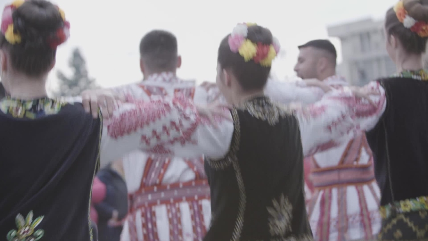 Pitesti/Romania - May 2019: Young people dressed in traditional costumes perform folk Romanian dances on the street
