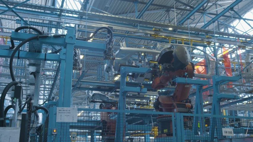 Car production industry. Automotive plant. Robots at the assembly line