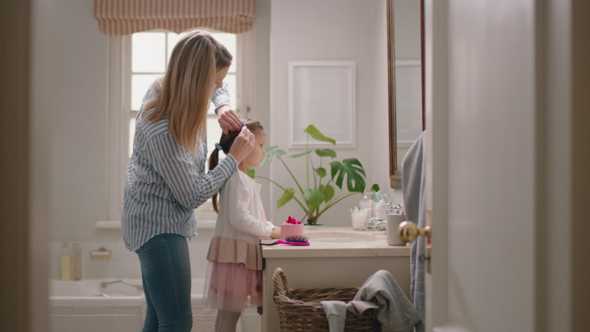 Happy mother brushing daughters hair in bathroom cute little girl getting ready in morning loving mom enjoying parenthood caring for child | Shutterstock HD Video #1034669186