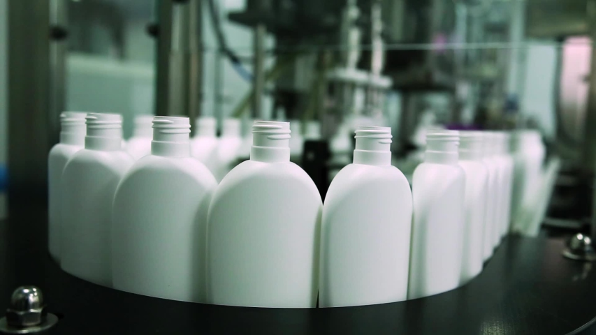 Cosmetics manufacturing plant. White bottles on the belt conveyor. Shampoo, shower gel and lotion.