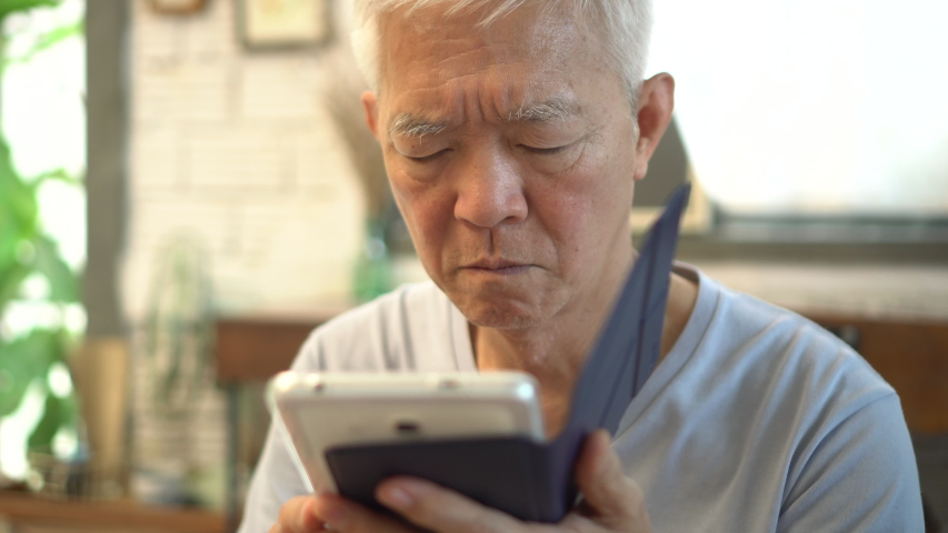 Asian elderly with bad eyesight can not see when using tablet | Shutterstock HD Video #1034693093
