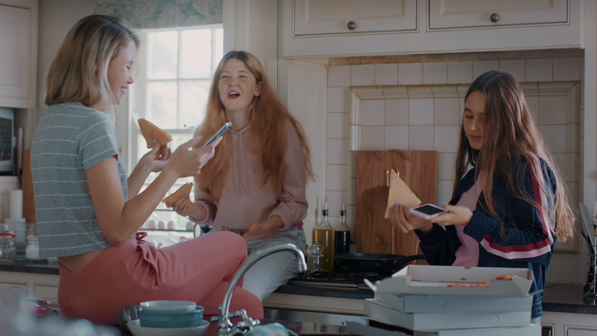 Group of teenage girls eating pizza in kitchen having fun chatting together using smartphones sharing lifestyle friends hanging out enjoying relaxing at home