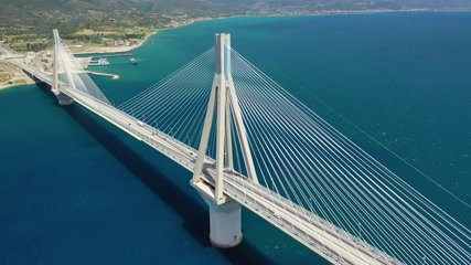 Aerial drone video of world famous cable suspension bridge of Rio - Antirio Harilaos Trikoupis, crossing Corinthian Gulf, mainland Greece to Peloponnese, Patras