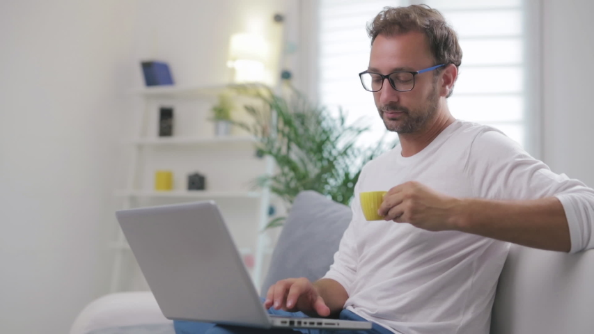 Man using laptop for video call in his living room. #1034707397