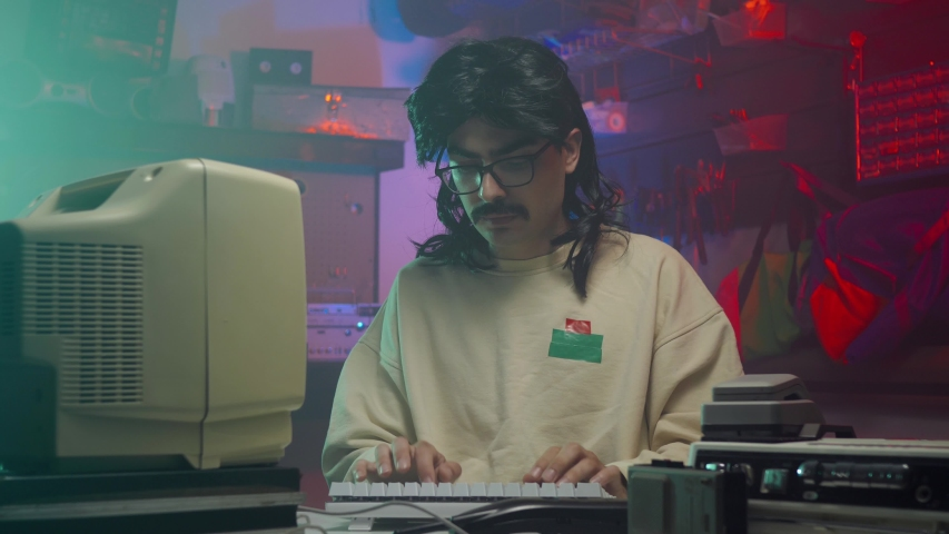 In the '80s or '90s young man answering the phone while using his personal computer typing on a keyboard. Retro scene with vintage colors and atmosphere. | Shutterstock HD Video #1034714279
