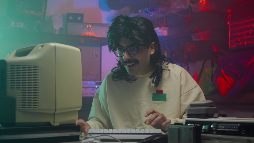 Happy computer nerd in the '80s or '90s using his personal computer. Retro scene with vintage colors and atmosphere.