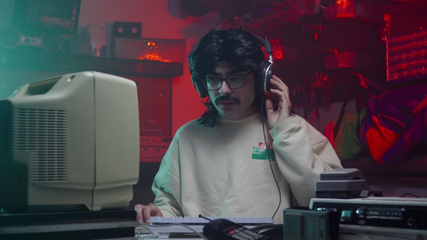Guy from the '80s or '90s listening music in front of his old computer screen. Retro scene with vintage colors and atmosphere.