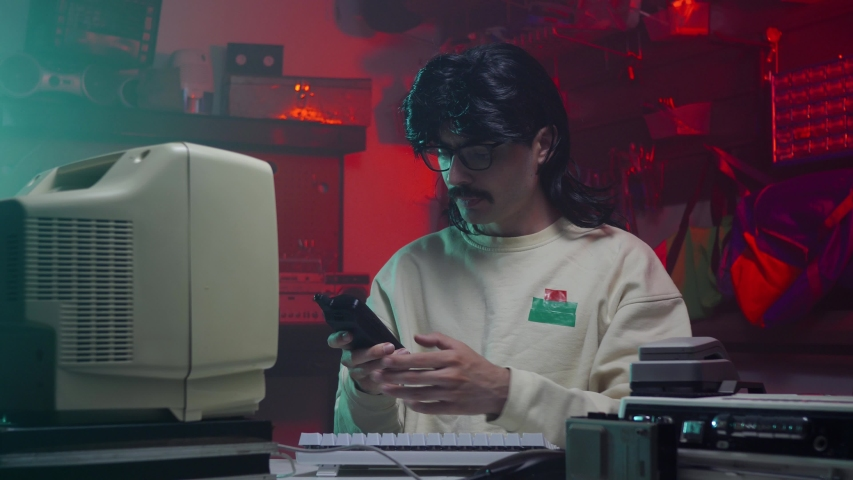 Computer nerd from the '80s or '90s using a cell telephone to place a call. Retro scene with vintage colors and atmosphere. | Shutterstock HD Video #1034714348