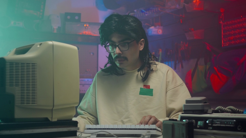 In the '80s or '90s young man using his personal computer typing on a keyboard. Retro scene with vintage colors and atmosphere. | Shutterstock HD Video #1034714354
