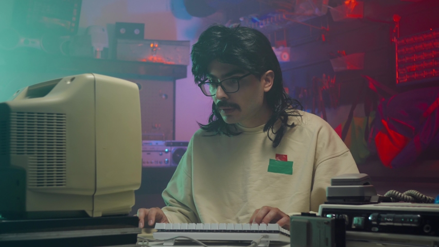 In the '80s or '90s young man using his personal computer typing on a keyboard. Retro scene with vintage colors and atmosphere. | Shutterstock HD Video #1034714375