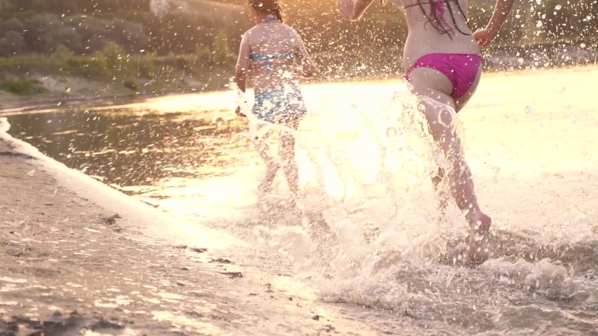 happy kids running along the beach. Girls run on sand along shore on beach splashing water drops and laughing. Happy and free teenagers on a summer vacation have rest at sunset. Teamwork #1034715149