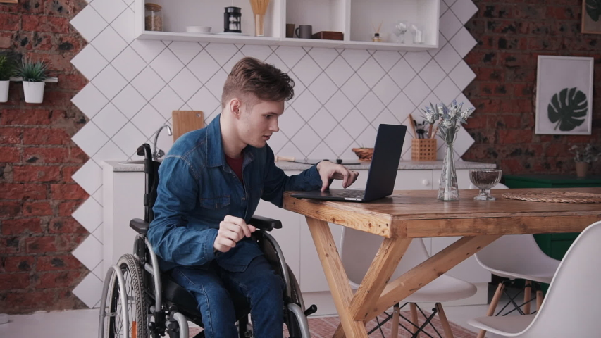 Adult disabled man self study working on laptop and checking news mail. Male wearing in denim jeans clothes, sitting in comfort wheel chair and spending his weekend at cozy house with modern room