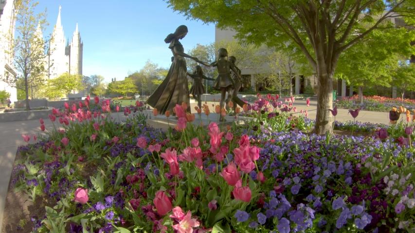 Salt Lake City , Utah / United States - 05 03 2019: Salt Lake City, Utah May 2019 - Spring flowers and a statue of children playing