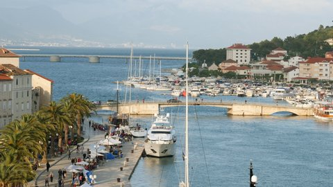 Boulevard with super yacht and stone bridge in historic village of Trogir, Croatia.