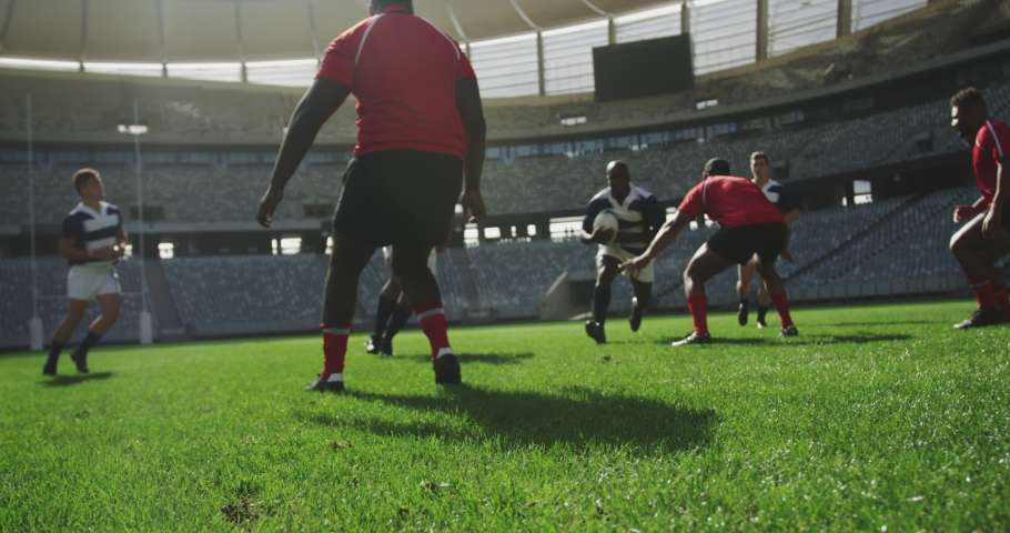 Front view of diverse rugby players playing rugby match in stadium. They are tackling each other in slow motion