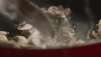 Close-up of chef with wooden spatula interferes with chopped champignon mushrooms in pan. Slow motion video