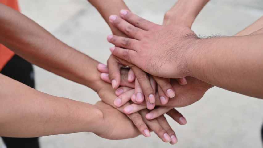 A group of friends extended their arms to touch their hands for unity. #1034748128