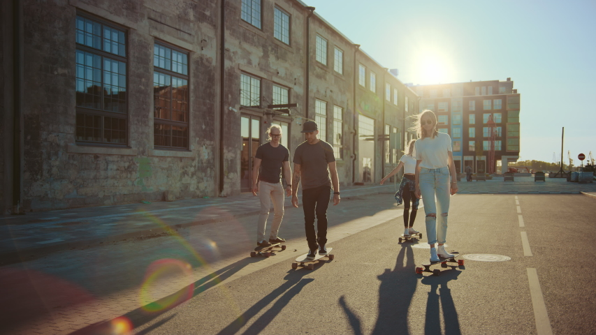 Group of Girls and Boys on Skateboards Through Fashionable Hipster District. Beautiful Young People Skateboarding Through Modern Stylish City Street. Moving Slow Motion Portrait Camera Shot