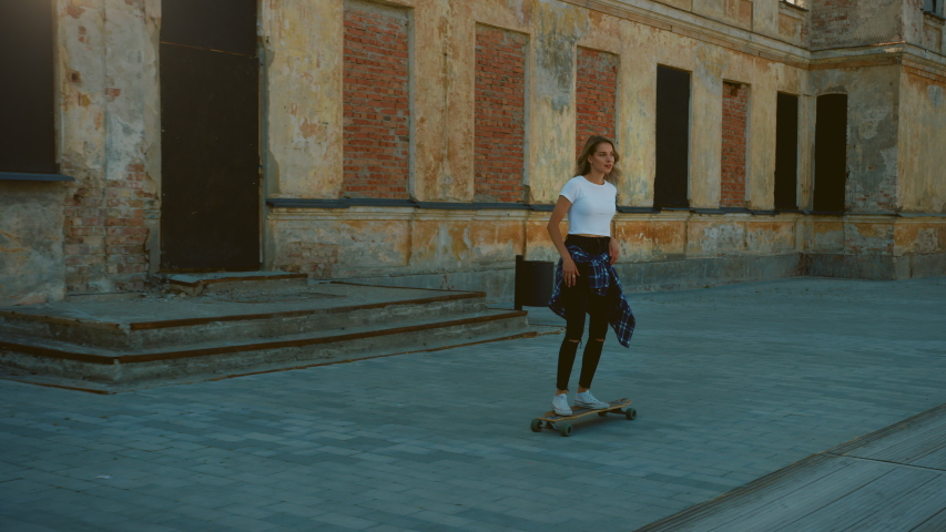 Beautiful Blonde Girl Riding on a Longboard through Hipster District. Stylish Teenager Skateboarding in the Cool Part of the City. Moving Slow Motion Camera Shot | Shutterstock HD Video #1034749271