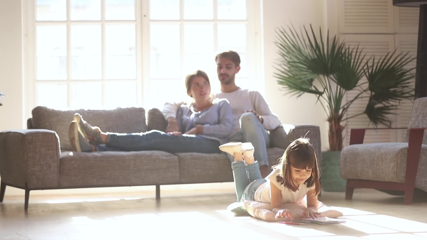 While little cutie daughter lying on warm floor with underfloor heating using colored pencils drawing on album young parents resting on couch, full family spending weekend at modern comfy home concept | Shutterstock HD Video #1034755961