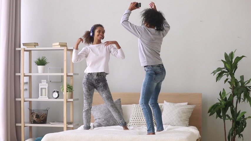 Black teen daughter wearing headphones have fun with mother use earphones enjoy listen favourite music on mobile phones apps dancing standing on bed at home, active hobby, good mood free time concept | Shutterstock HD Video #1034756018