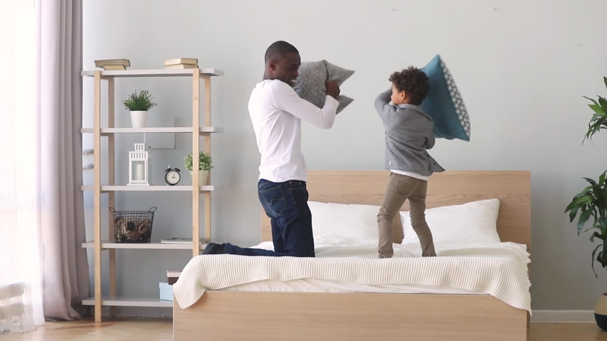 African father enjoying pillow fight with little mixed race son on bed at home, carefree funny older younger brothers spend free time on weekend together play active game holding cushions having fun | Shutterstock HD Video #1034756084