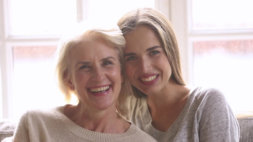 Head shot portrait of laughing grown up daughter hugging middle aged mother relative people sit on couch feels overjoyed posing looking at camera, good relations between different generations concept | Shutterstock HD Video #1034756093