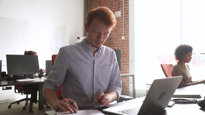 Redhead focused office worker manager sit in coworking space office having busy workday read documentations sales statistics using pc typing preparing report or presentation, analyzes data information | Shutterstock HD Video #1034756105