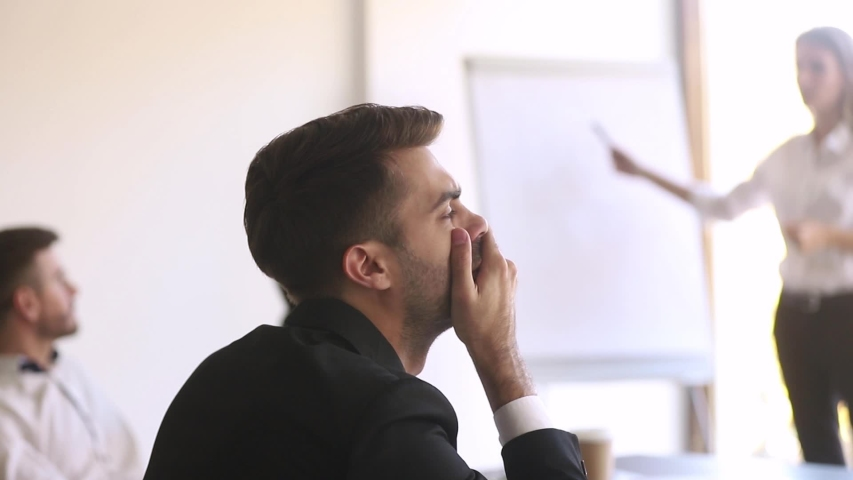 People takes parts participating at seminar workshop listens information given by trainer, close up focus on yawning employee feels bored disinterested during presentation training in boardroom office | Shutterstock HD Video #1034756228