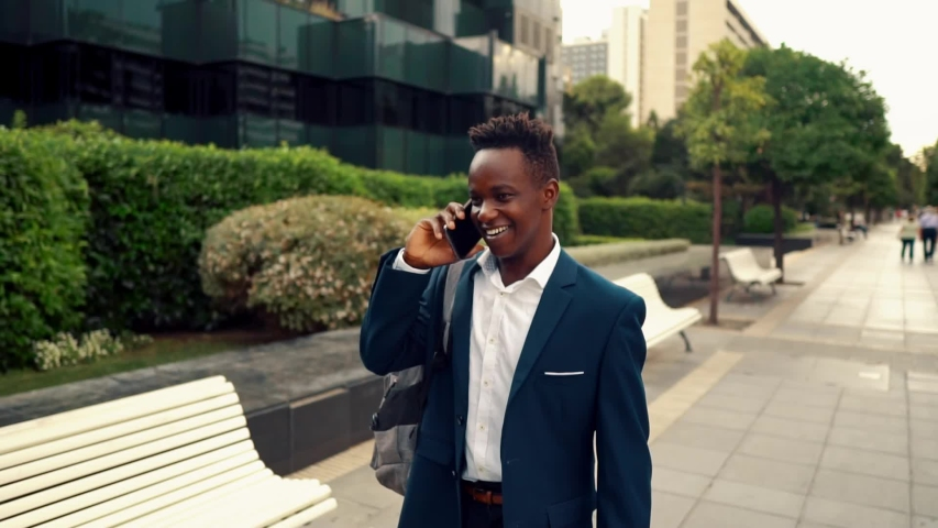 African American businessman wearing blue suit, walking and using modern smartphone near office. Business concept   Shutterstock HD Video #1034757350