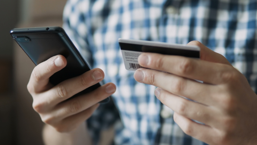 Close up shot of a man buying online with smart phone and credit card - Online shopping. People making a purchase using a credit card online.