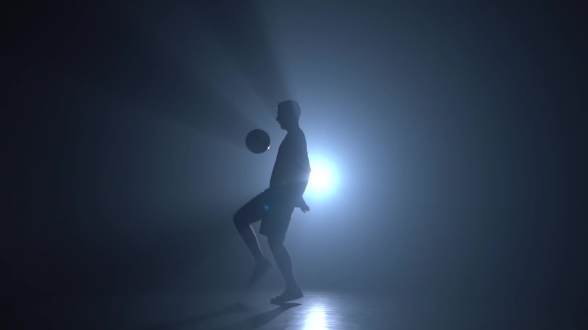 Silhouette of football freestyler stuffing the ball and making tricks in a twilight against a light of studio. Slow motion | Shutterstock HD Video #1034762798