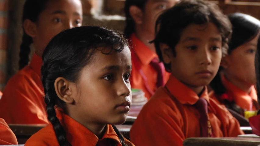 Kathmandu / Nepal - 04 27 2019: Close up on group of male & female young students dressed in orange school uniforms, listening quietly to teacher giving lesson in Kathmandu classroom. | Shutterstock HD Video #1034769797