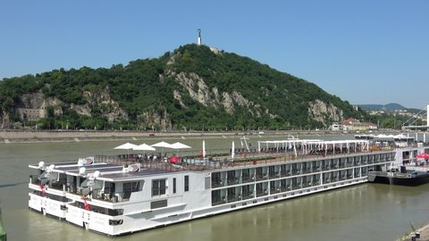 Hungary, Budapest, June 12, 2019. View of river Dunabe with cruise boat and Hungarian Liberty Statue on the top of Gellert Hill.