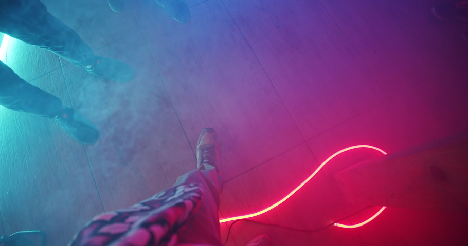 First-person view young man walking on the dance floor among his cheerful friends. Top view friendly people feet dancing together into music in nightclub. Colorful neon illumination interior.