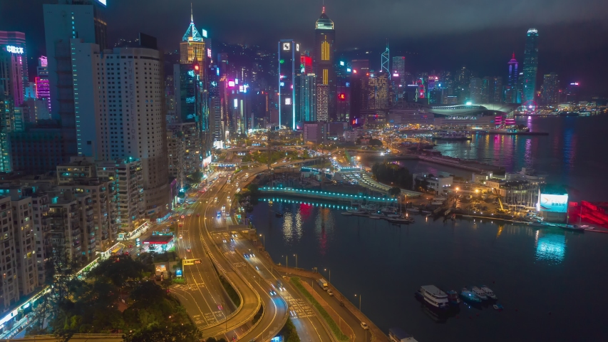Aerial drone hyper lapse or time lapse over Hong Kong Victoria Harbor at night. Central distinct of Hong Kong shot by 4K resolution drone, Hong Kong is the most densely populated place in the world.
