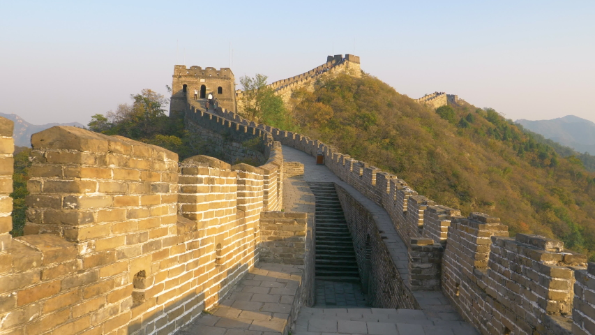 Stone stairwell leads up to the path on top of the majestic Great Wall of China. Stunning view of the ancient stone wall in rural China illuminated by the golden evening sun. Great Wall at sunrise.