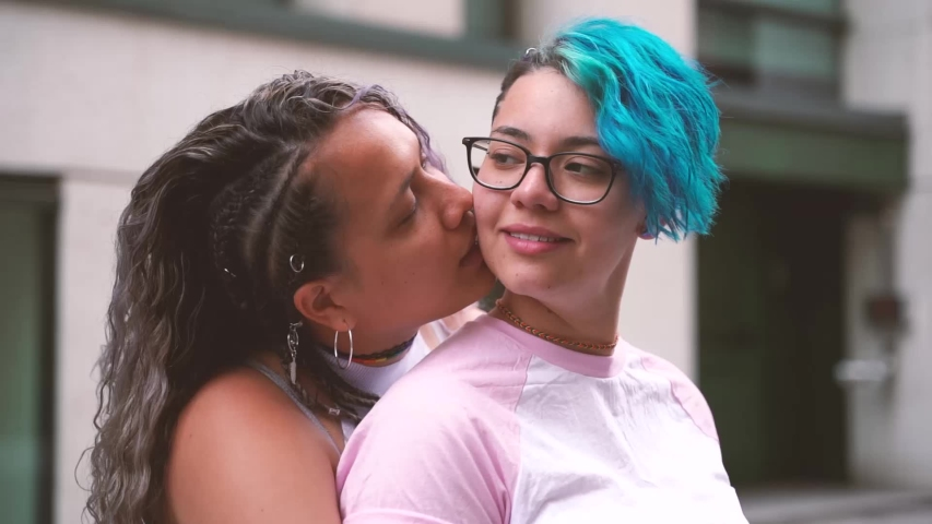 Modern cool young lesbian girlfriends in love. Woman kissing her fiance neck in public. Lesbian couple kissing in a public place. Not embarrassed of their sexuality. Proud to be gay.  #1034823851