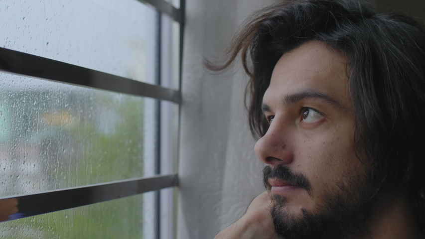 Man Looking Out Of Window at Rain. Day Dream, Pondering and Thinking Concept.