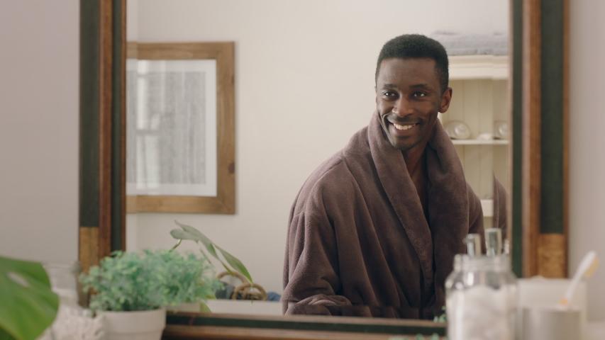 happy african american man dancing in bathroom looking in mirror having fun morning routine getting ready enjoying positive self image wearing bathrobe #1034850533