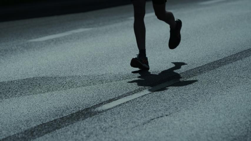 Running marathon. Close up on runners feet. Shadows on the street. Royalty-Free Stock Footage #1034852633