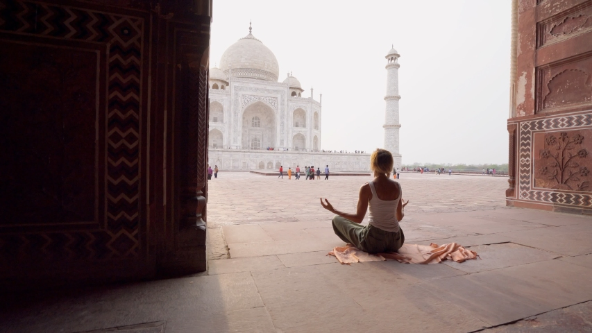 Young woman practicing yoga in India at the famous Taj Mahal at sunrise - People travel spirituality zen like concept - Girl doing yoga