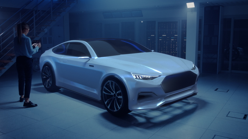 Female Automotive Engineer Uses Digital Tablet with Augmented Reality for Car Design Improvement. 3D Graphics Visualization Shows Fully Developed Vehicle Prototype With Turned On Headslights   Shutterstock HD Video #1034861843